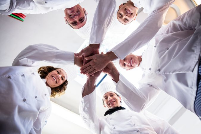 Portrait of chefs team putting hands together and cheering in a